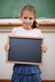 Portrait d'une jeune fille se tenant à une ardoise d'école Image stock