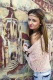 Portrait d'une jeune fille se tenant prêt le mur avec un graphite peint photos stock