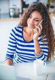 Portrait d'une jeune jolie femme parlant le téléphone et travaillant sur l'ordinateur portable dans la cuisine Photo stock
