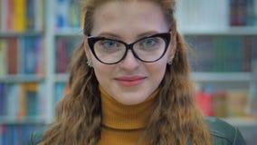 Portrait d'une jeune jolie femme souriante jeune fille en verre Lecture d'un livre à la bibliothèque de l'université de la vill banque de vidéos