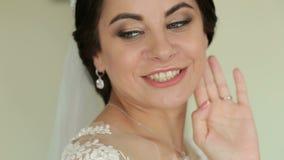 Portrait d'une jeune mariée aux yeux bleus mignonne dans une robe l'épousant banque de vidéos