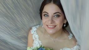 Portrait d'une jeune mariée avec un bouquet des fleurs dans des ses mains près de la fenêtre clips vidéos
