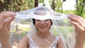 Portrait d'une jeune mariée heureuse dans un voile avec une tête couverte en parc d'été banque de vidéos