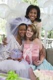 Portrait d'une jeune mariée tenant le cadeau avec sa mère et ami Images libres de droits