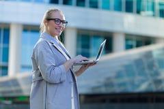 Portrait d'une jeune position de femme d'affaires avec un ordinateur portable au centre de la ville photos libres de droits
