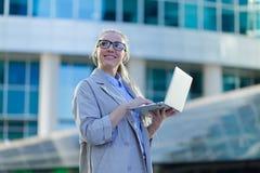 Portrait d'une jeune position de femme d'affaires avec un ordinateur portable au centre de la ville photographie stock libre de droits