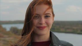 Portrait d'une jolie femme aux cheveux rouges souriant assez confiant Météo, automne, printemps banque de vidéos