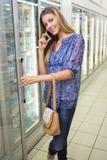 Portrait d'une jolie femme blonde de sourire achetant les produits congelés et téléphoner Photo libre de droits