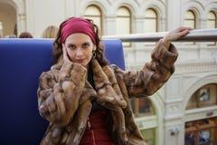 Portrait d'une jolie femme dans le manteau de fourrure au centre de boutique Image stock