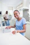 Portrait d'une jolie femme de sourire heureuse à l'aide de son ordinateur portable Image libre de droits