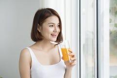 Portrait d'une jolie femme jugeant de verre avec du jus savoureux Mode de vie sain, régime végétarien et repas Jus de boissons So image stock