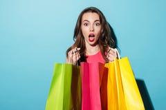 Portrait d'une jolie fille choquée tenant les paniers colorés Image libre de droits