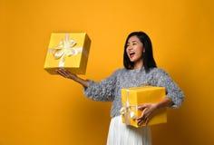 Portrait d'une jolie fille de sourire jugeant deux boîte-cadeau d'isolement au-dessus du fond jaune image libre de droits