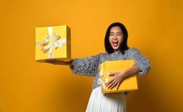 Portrait d'une jolie fille de sourire jugeant deux boîte-cadeau d'isolement au-dessus du fond jaune images stock