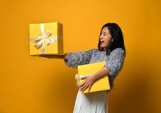 Portrait d'une jolie fille de sourire jugeant deux boîte-cadeau d'isolement au-dessus du fond jaune photographie stock libre de droits