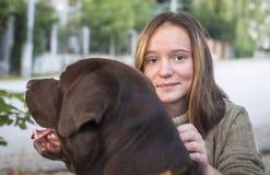 Portrait d'une jolie fille marchant dehors avec un grand chien Images stock