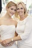 Portrait d'une mère avec la fille habillée comme jeune mariée dans le magasin nuptiale Photographie stock libre de droits