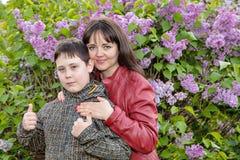 Portrait d'une mère avec son fils adolescent dans un jardin lilas de floraison Photos stock