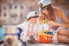 Portrait d'une mère avec son fils jouant sur la jetée par la mer dans la ville, toujours photo de la vie Images stock