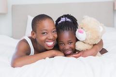 Portrait d'une mère de sourire assez belle avec sa fille dans son lit photographie stock libre de droits