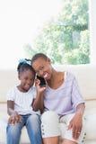 Portrait d'une mère de sourire heureuse téléphonant avec sa fille sur le divan photo stock