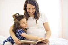 Portrait d'une mère et d'une fille lisant un livre se trouvant et détendre dans le lit photographie stock libre de droits