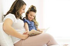 Portrait d'une mère et d'une fille lisant un livre se trouvant et détendre dans le lit photo stock