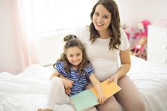 Portrait d'une mère et d'une fille lisant un livre se trouvant et détendre dans le lit images stock