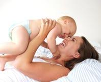 Portrait d'une mère gaie et de jouer mignon de bébé Image stock