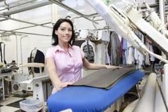 Portrait d'une machine repassante se tenante prêt de mi femme adulte heureuse dans la blanchisserie photos stock