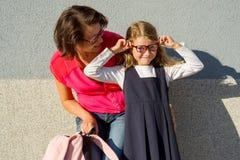 Portrait d'une maman et d'une fille d'une petite écolière avec Glasse Photos stock