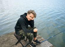 Portrait d'une pêche d'adolescent sur la banque de la rivière ou du lac Garçon mignon avec les cheveux bouclés photos libres de droits