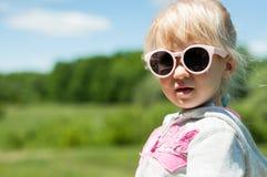 Portrait d'une petite des lunettes de soleil de port mignonnes fille Photographie stock libre de droits