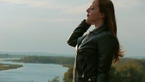 Portrait d'une petite femme aux cheveux rouges debout sur une colline, sur le fond de la nature, paysage pittoresque clips vidéos