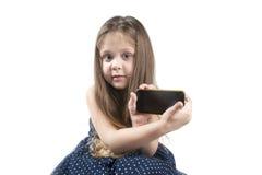 Portrait d'une petite fille avec le téléphone portable à disposition Image stock