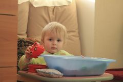 Portrait d'une petite fille blonde aux yeux bleus avec ses jouets à la maison Image libre de droits
