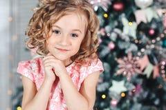Portrait d'une petite fille blonde avec des boucles près d'un arbre avec les lanternes et les drapeaux brillamment colorés Photographie stock libre de droits