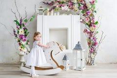 Portrait d'une petite fille blonde en fleurs Elle se tiennent près du balancier en bois de cheval dans la salle de fleurs blanche Image libre de droits