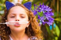 Portrait d'une petite fille bouclée heureuse jouant avec des bulles de savon sur une nature d'été, port oreilles bleues de tigre Photographie stock