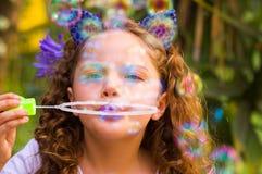 Portrait d'une petite fille bouclée heureuse jouant avec des bulles de savon sur une nature d'été, port oreilles bleues de tigre Images stock