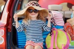 Portrait d'une petite fille dans le tronc d'une voiture Photos stock