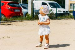 Portrait d'une petite fille dans une robe blanche et un chapeau blanc avec des fleurs sur le fond des voitures, sur le terrain de photo libre de droits