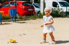 Portrait d'une petite fille dans une robe blanche et un chapeau blanc avec des fleurs sur le fond des voitures, sur le terrain de photo stock