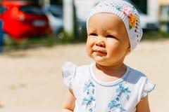 Portrait d'une petite fille dans une robe blanche et un chapeau blanc avec des fleurs sur le fond des voitures, sur le terrain de photos stock