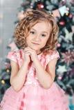 Portrait d'une petite fille dans une robe rose près d'un arbre de Noël Photo stock