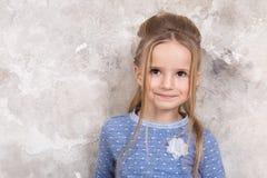Portrait d'une petite fille de sourire attirante dans un chandail bleu et le pantalon avec des cheveux pli?s dans ses cheveux con photos stock