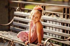 Portrait d'une petite fille de sourire s'asseyant sur un banc de parc Images stock