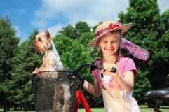Portrait d'une petite fille dehors avec le vélo et le chien Images libres de droits