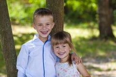 Portrait d'une petite fille et d'un garçon étreignants de sourire un jour ensoleillé Photo stock