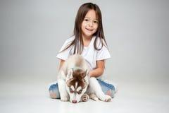Portrait d'une petite fille joyeuse ayant l'amusement avec le chiot enroué sibérien sur le plancher au studio images libres de droits